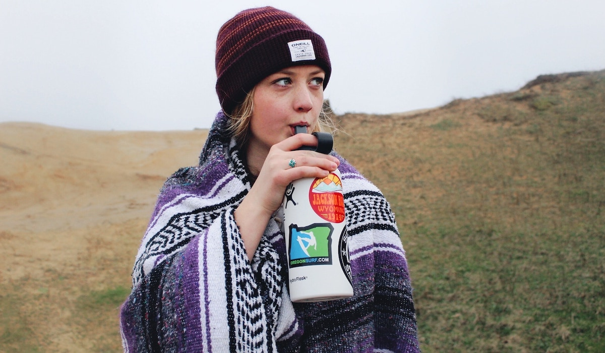 woman drinking water from white bottle