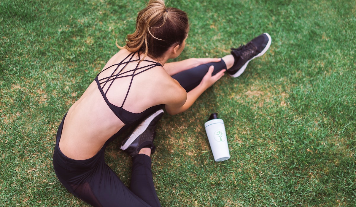 woman in black yoga pants holding white bottle photo