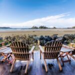 Four Brown Adirondack Chairs On Porch