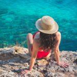 Woman in Blue Bikini Wearing Brown Straw Hat Sitting on Rock in Mallorca